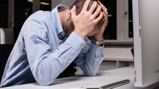 デスクトップで頭をかかえる男性